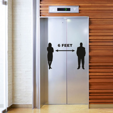 Elevator with social distancing signs and decals.